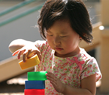 Toddler girl playing with blocks.