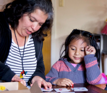 A young female child with caregivers learning early education
