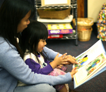Photo of parent showing a toddler a book.